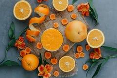 Kvinnlign räcker den hållande orange smoothien som dekoreras med alstroemeria med den orange pajen Arkivfoto