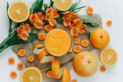 Kvinnlign räcker den hållande orange smoothien som dekoreras med alstroemeria med den orange pajen Royaltyfri Foto
