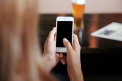 Kvinnlign räcker den hållande smartphonen Arkivbilder