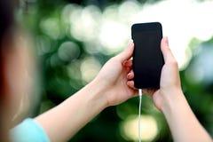 Kvinnlign räcker den hållande smartphonen Royaltyfri Foto