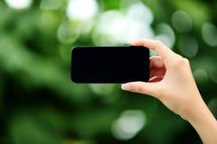 Kvinnlign räcker den hållande smartphonen Royaltyfri Fotografi