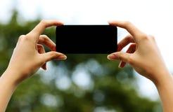 Kvinnlign räcker den hållande smartphonen Royaltyfri Bild