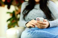 kvinnlign räcker den hemmastadda hållande smartphonen. Fokus på telefonen Arkivbilder