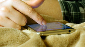 Kvinnlign räcker den rörande smartphonen, medan ligga på sängarket royaltyfria bilder