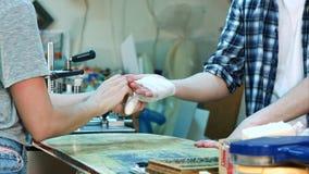 Kvinnlign räcker försiktigt att förbinda arbetaren sårade handen efter olycka Arkivbild