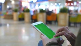 Kvinnlign räcker genom att använda den moderna smartphonen med den gröna skärmen Ung flickasammanträde på bänken i shoppinggaller lager videofilmer