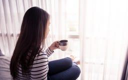 Kvinnlign räcker hållande coffeecup på säng Fotografering för Bildbyråer