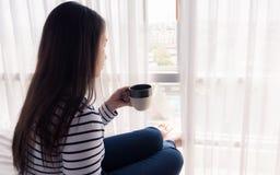 Kvinnlign räcker hållande coffeecup på säng Arkivfoton