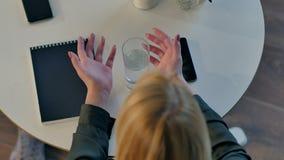 Kvinnlign räcker hållande exponeringsglas av vatten i kafé lager videofilmer