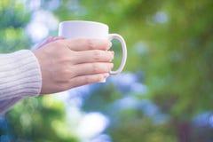 Kvinnlign räcker hållande koppar kaffe Arkivbild