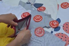 Kvinnlign räcker hållande tom handväskabakgrund med kläder med rabattetiketter Royaltyfria Foton