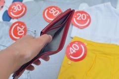 Kvinnlign räcker hållande tom handväskabakgrund med lothes med rabattetiketter Arkivfoto