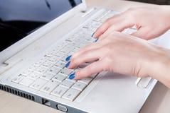 Kvinnlign räcker handstil på bärbar datortangentbordet i regeringsställning royaltyfri bild