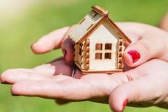 Kvinnlign räcker innehavet och besparingen det lilla trähuset Hushållbegrepp Royaltyfri Foto