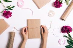 Kvinnlign räcker inpackning av gåvor för ferien på en vit backgroun royaltyfria bilder