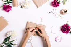 Kvinnlign räcker inpackning av gåvor för ferien på en vit tabell royaltyfri bild
