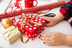 Kvinnlign räcker inpackning av xmas-gåvor in i pappers- och band dem upp wi royaltyfri foto