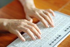 Kvinnlign räcker maskinskrivning på ett PCtangentbord Arkivbild