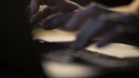 Kvinnlign räcker maskinskrivning på tangentbordet på den moderna bärbar datordatoren i mörk inre arkivfilmer