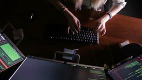 Kvinnlign räcker maskinskrivningdatorkoden, dataintrångdator på ett mörkt rum En hacker programmerare på arbete lager videofilmer