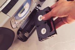Kvinnlign räcker mellanläggskassetten in i musikcentrum royaltyfria foton