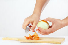 Kvinnlign räcker skalning av den rå löken med en kniv på en skärbräda Fotografering för Bildbyråer