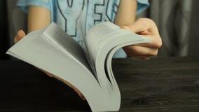 Kvinnlign räcker att vända sidorna av en bok snabbt, tätt upp arkivfilmer