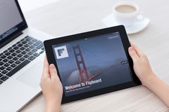 Kvinnlign räcker hållande iPad med app Flipboard på skärmen i th Royaltyfria Bilder