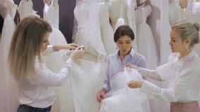 Kvinnlign shoppar konsulenthjälp som bruden väljer klänningen på shoppar av bröllopmode Fokus på flicka lager videofilmer