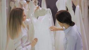 Kvinnlign shoppar konsulenthjälp som bruden väljer klänningen på shoppar av bröllopmode Fokus på flicka arkivfilmer
