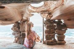 Kvinnlign sitter inom klippaöverkantgrottan som håller ögonen på havet royaltyfria bilder