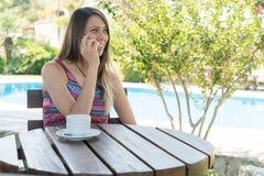 Kvinnlign sitter vid pölen på sommar Tid talar nära med mobiltelefonen Bozcaada Canakkale i Turkiet 2017 Arkivfoton