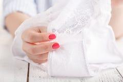 Kvinnlign snör åt vit underbyxor i hand på vit bakgrund arkivbilder