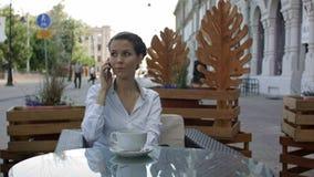 Kvinnlign som kallar via mobiltelefonen till hennes partner för berättar om resultaten för månatlig inkomst vilket hon mottog via Royaltyfria Bilder