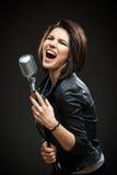 Kvinnlign vaggar den hållande mikrofonen för musikern Fotografering för Bildbyråer