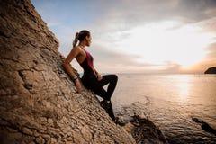 Kvinnlign vaggar hållande ögonen på solnedgång för klättrare över havet Arkivbilder