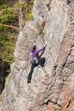 Kvinnlign vaggar klättraren på en klippa Arkivfoton