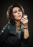 Kvinnlign vaggar musikern med mic royaltyfri bild