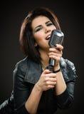 Kvinnlign vaggar musikern som håller mic arkivbild