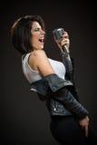 Kvinnlign vaggar musikern som håller mikrofonen royaltyfri fotografi