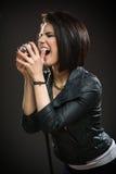 Kvinnlign vaggar musikern som räcker mikrofonen royaltyfri foto
