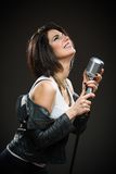 Kvinnlign vaggar musikern som rymmer mic Arkivfoton