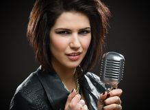 Kvinnlign vaggar sångaren med mic royaltyfri foto