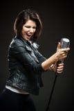 Kvinnlign vaggar sångaren som håller mikrofonen Royaltyfria Foton