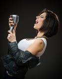 Kvinnlign vaggar sångaren som räcker mic arkivfoton