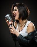 Kvinnlign vaggar sångaren som räcker mikrofonen arkivfoto