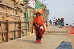 Kvinnlign vallfärdar bär packen på hennes huvud på väg till den nästa templet Royaltyfria Bilder
