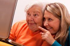 Kvinnligpensionären med bärbar dator har gyckel Arkivbild