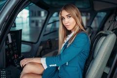 Kvinnligpilot i hörlurar i helikopterkabin arkivfoto