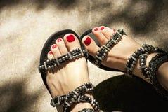 Kvinnligs fot i lädersandaler Arkivfoto